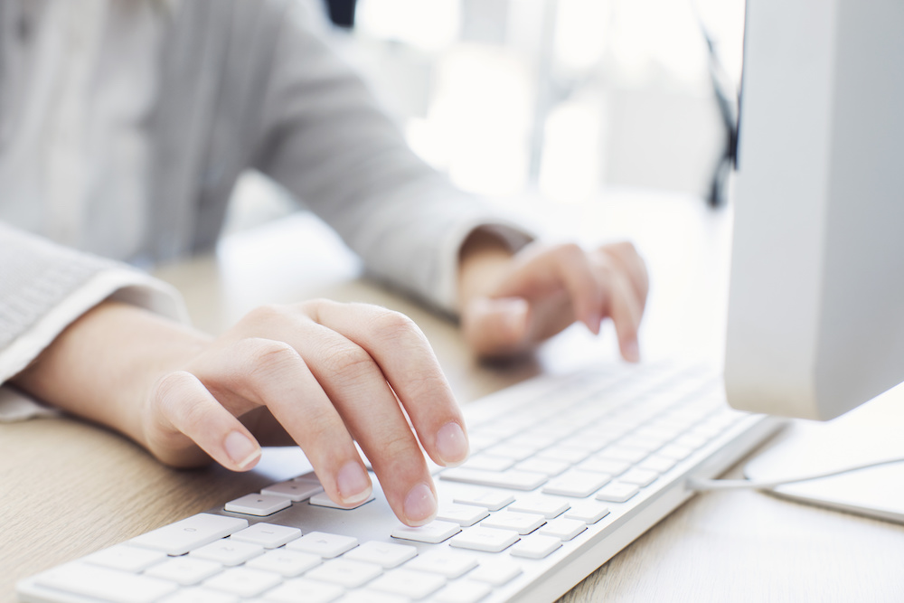 Woman typing on office keyboard