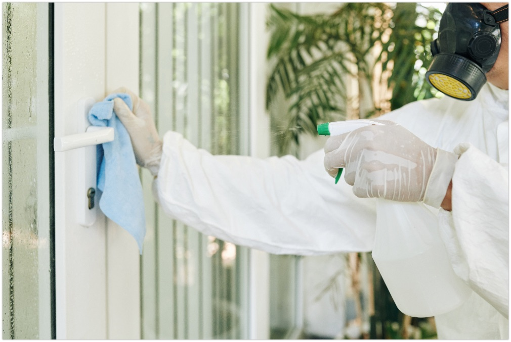 Cleaning service worker sparying disinfecting detergent on door handle